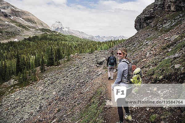Portrait smiling woman hiking on craggy mountain trail  Yoho Park  British Columbia  Canada