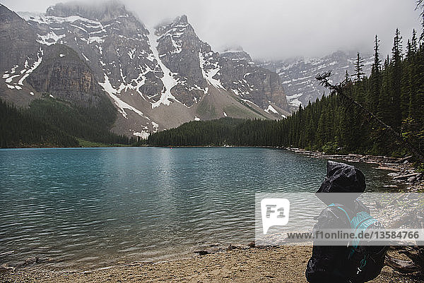 Serene hiker in rain jacket enjoying tranquil mountain and lake view  Banff  Alberta  Canada