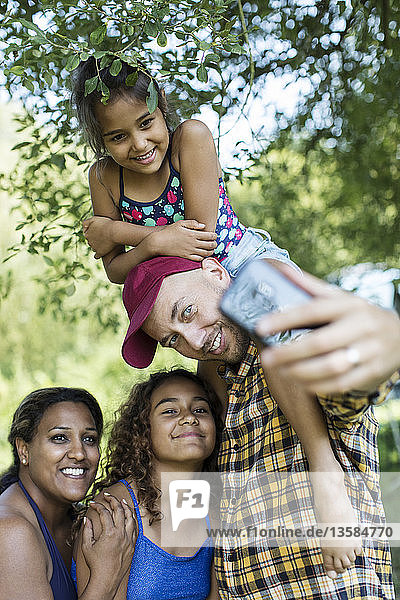 Happy  affectionate family taking selfie with camera phone