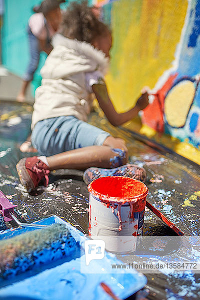 Girl painting mural behind paint can
