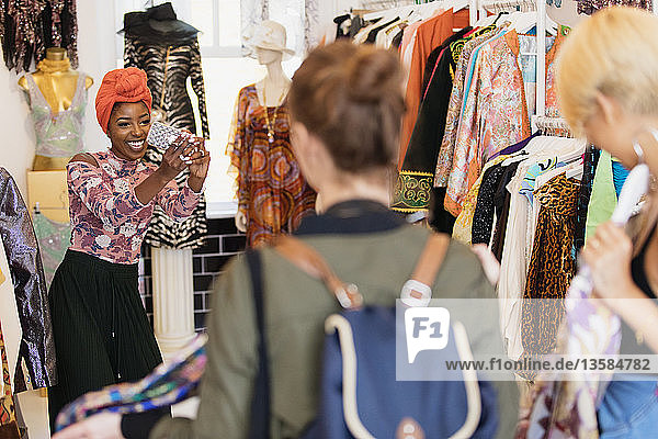 Young woman with camera phone photographing friends shopping in clothing store