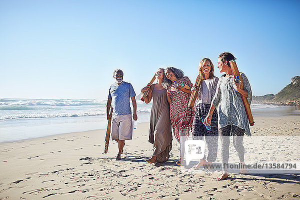 Friends walking with yoga mats on sunny beach during yoga retreat