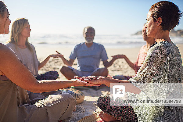 Serene people meditating in circle on sunny beach during yoga retreat