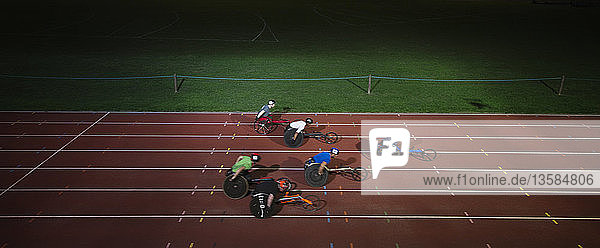 Paraplegic athletes racing along sports track in wheelchair race in night