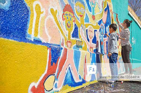 Mother and son volunteers painting vibrant mural on sunny wall