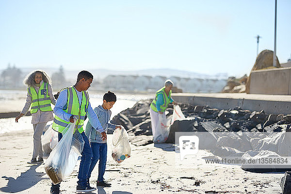 Father and son volunteers cleaning up litter on sunny beach
