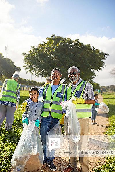Portrait happy multi-generation men volunteering  cleaning up litter in sunny park
