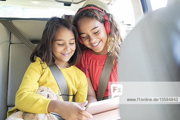 Sisters using digital tablet in back set of car