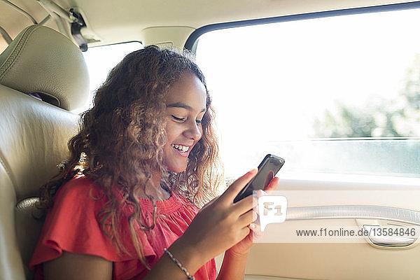 Smiling tween girl using smart phone in back seat of car