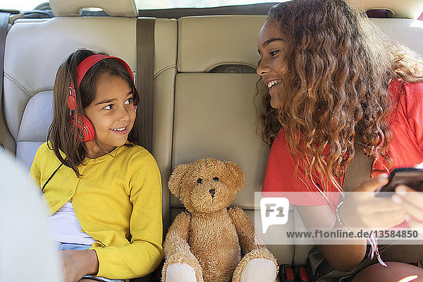 Sisters and teddy bear riding in back set of car