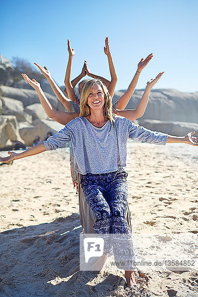 Portrait happy yoga class with arms outstretched behind woman on sunny beach during yoga retreat
