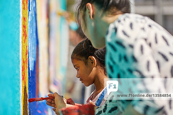 Teacher and elementary girl student painting on wall