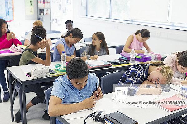 Junior high school students studying at desks in classroom