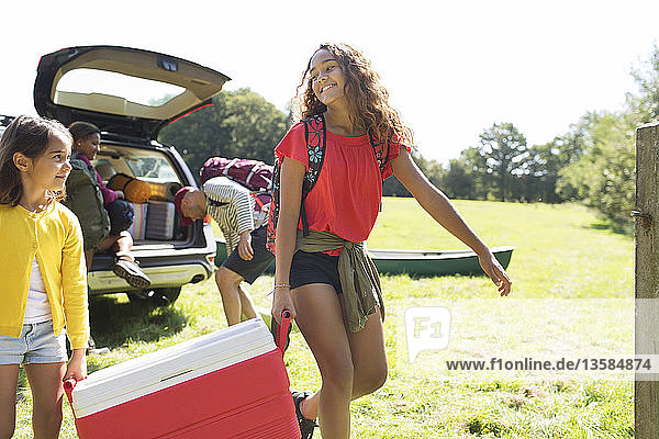 Sisters camping  carrying cooler in sunny field