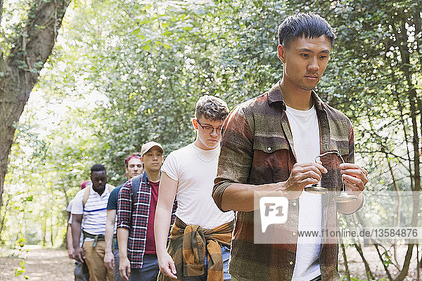 Man with tingsha cymbals leading mens group hike in woods