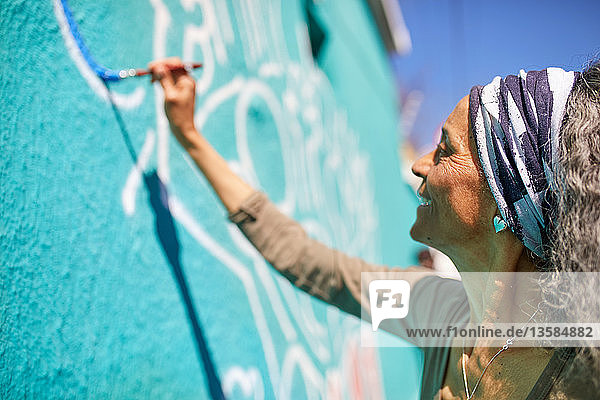 Senior woman painting mural on sunny wall