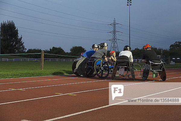 Paraplegic athletes huddling on sports track  training for wheelchair race at night