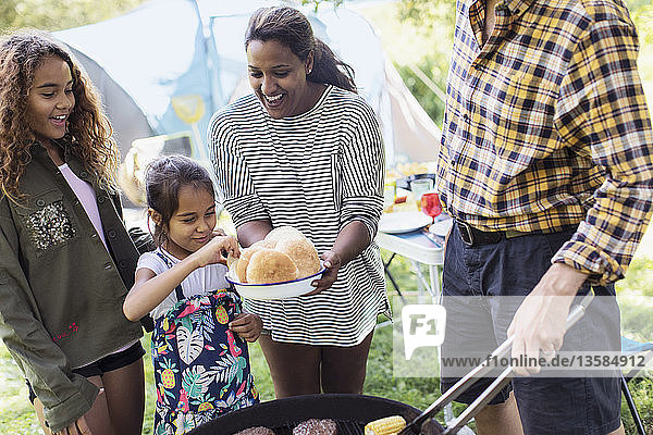 Family barbecuing hamburgers at campsite