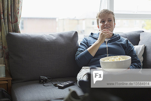 Young woman eating popcorn on sofa