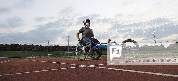 Determined young female paraplegic athlete training for wheelchair race on sports track