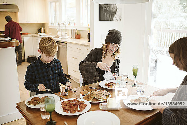 Family eating breakfast at kitchen table