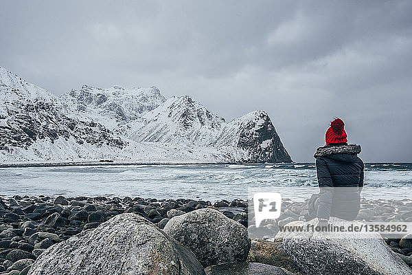Woman in warm clothing enjoying remote snowy ocean and mountain view  Lofoten Islands  Norway
