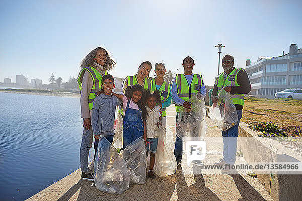 Portrait happy volunteers picking up litter on sunny boardwalk