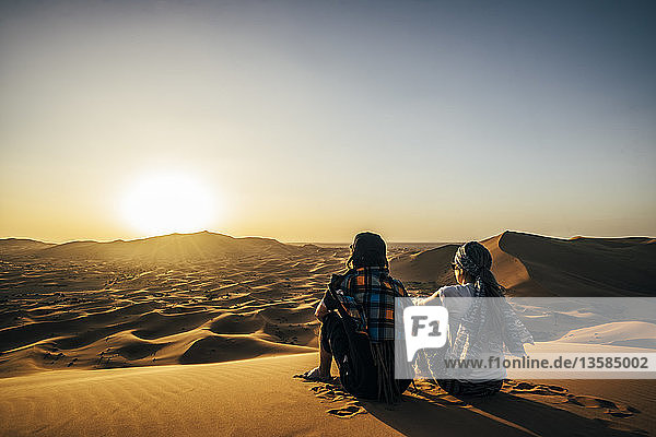 Couple enjoying sunny scenic view of remote  sandy desert  Sahara  Morocco