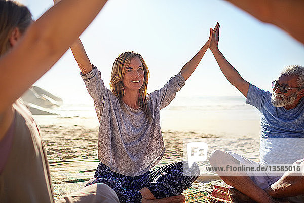 Happy friends joining hands in circle on sunny beach during yoga retreat