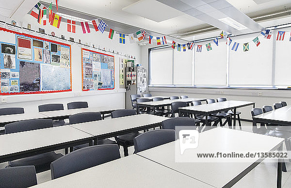 International flags hanging over desks in classroom