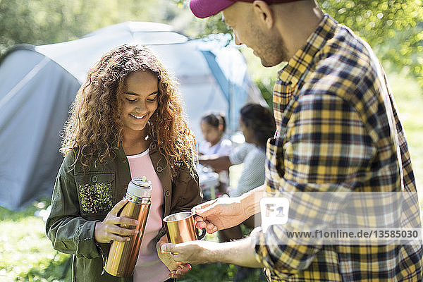 Daughter pouring coffee from insulated drink container for father at campsite