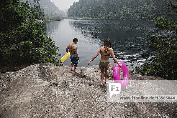 Young couple with inflatable rings at remote lakeside  Squamish  British Columbia  Canada