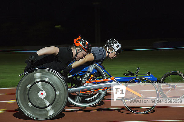 Paraplegic athletes speeding along sports track during wheelchair race at night