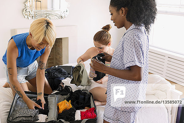 Young women friends packing for spring break in bedroom