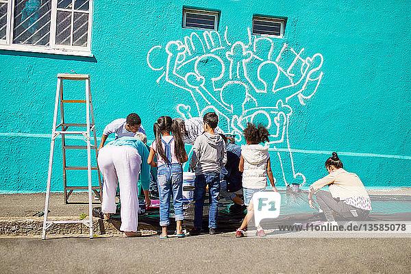 Kid volunteers painting community mural on sunny wall