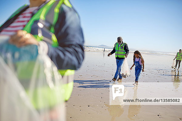 Grandfather and granddaughter volunteers cleaning up litter on sunny wet sand beach