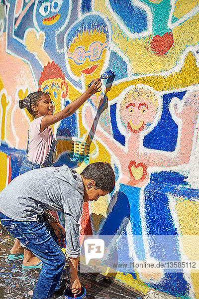 Children painting vibrant mural on sunny wall