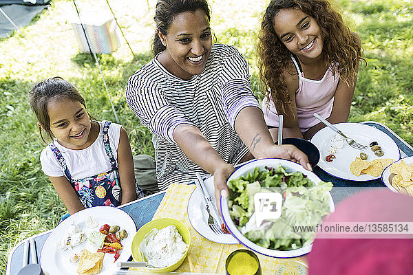 Happy mother and daughters enjoying salad lunch at campsite table