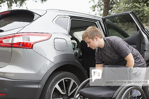Young woman loading wheelchair into back seat of car