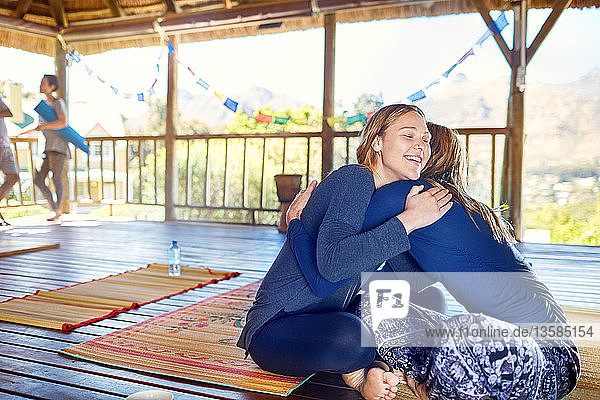 Happy mother and daughter hugging on yoga mats in hut during yoga retreat