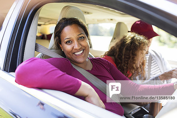 Portrait happy woman in car with family on road trip