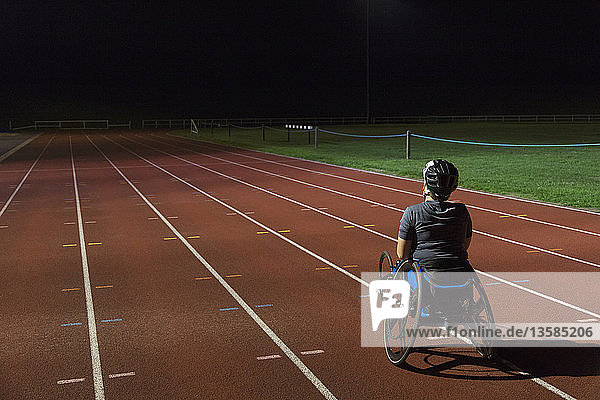 Determined female paraplegic athlete training for wheelchair race on sports track at night