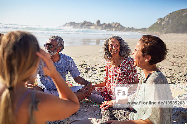 Friends sitting in circle on sunny beach during yoga retreat