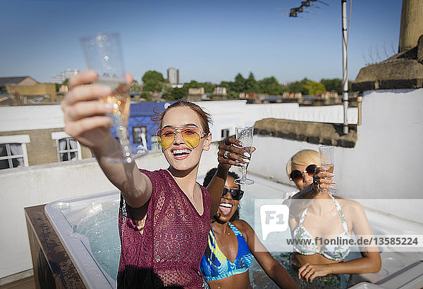 Portrait confident  carefree young women friends drinking champagne in sunny rooftop hot tub
