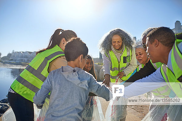 Volunteers forming huddle  cleaning up litter on sunny beach