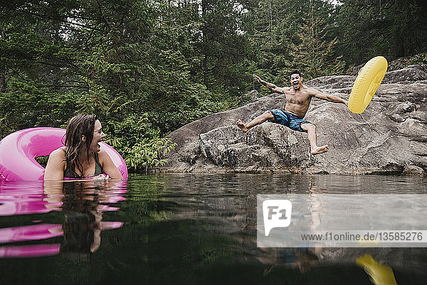 Playful young man with inflatable ring jumping into remote lake  Squamish  British Columbia  Canada