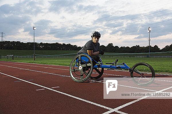 Portrait confident female paraplegic athlete training for wheelchair race on sports track