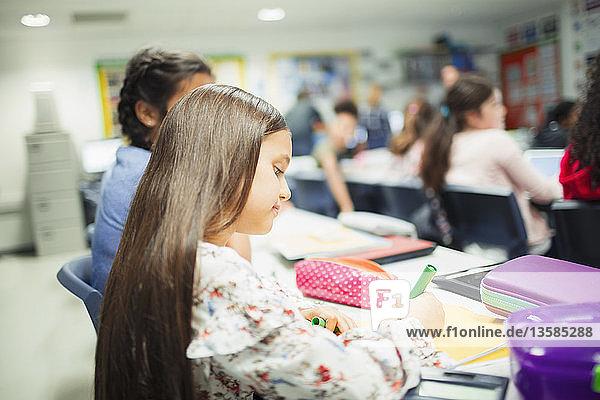 Junior high school girl student doing homework at desk in classroom