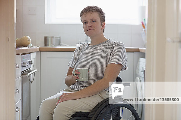Portrait confident young woman in wheelchair drinking tea in apartment kitchen