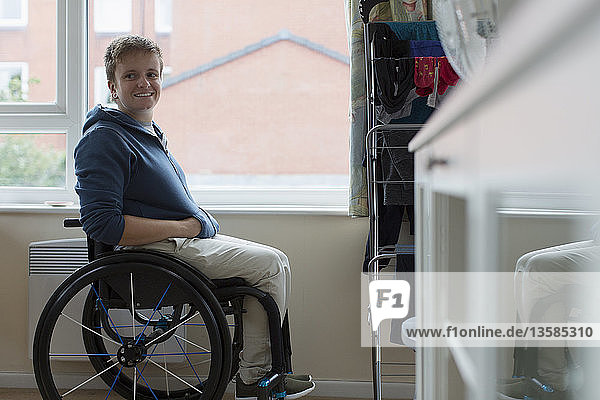 Portrait confident young woman sitting in wheelchair at window